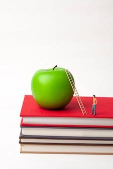 Uomo in miniatura in piedi e mela sulla pila di libri nuovi