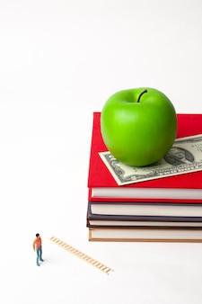 Uomo in miniatura in piedi con la mela sulla pila di libri nuovi