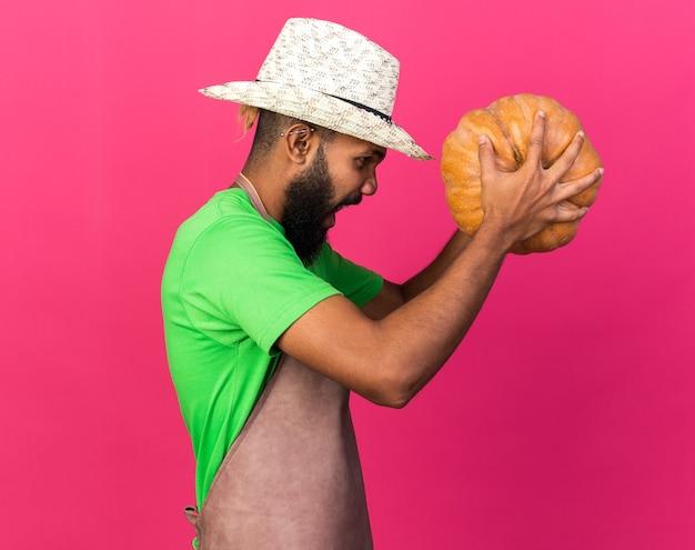 In piedi in vista di profilo giovane giardiniere arrabbiato ragazzo afroamericano che indossa un cappello da giardinaggio che tiene zucca
