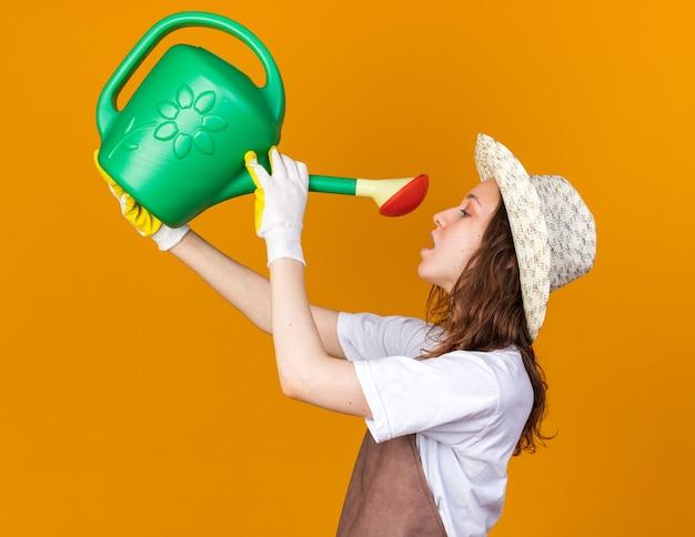 In piedi in vista di profilo giovane giardiniere femminile che indossa cappello e guanti da giardinaggio che si innaffia con un annaffiatoio isolato su una parete arancione
