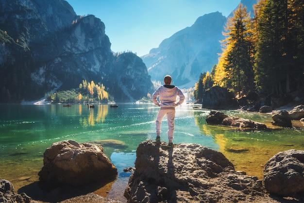 Uomo sportivo diritto sulla pietra sulla costa del lago braies ad alba