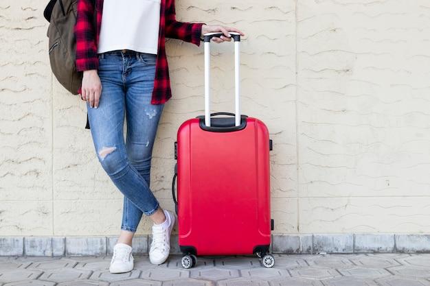 Donna in piedi viaggiatore con bagagli Foto Premium