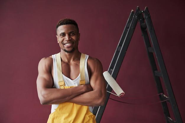 In piedi con le braccia incrociate. il giovane operaio afroamericano in uniforme gialla ha qualche lavoro