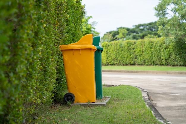 In piedi il bidone della spazzatura giallo e verde al campo