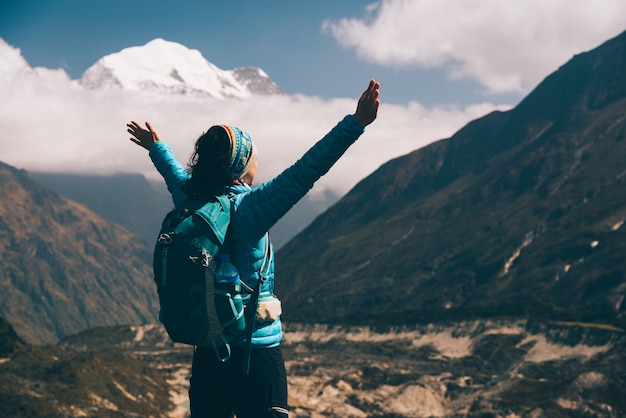 Giovane donna diritta con lo zaino e le armi alzate su sulla collina e guardare sulle montagne