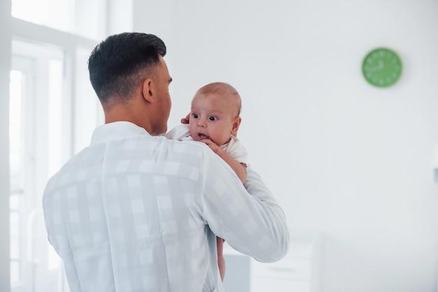 Si alza e tiene il bambino sulle mani. il giovane pediatra è in clinica durante il giorno.