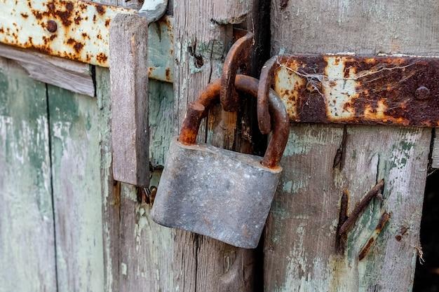 La graffetta della serratura rotta è segata e incernierata sulla vecchia porta di legno.