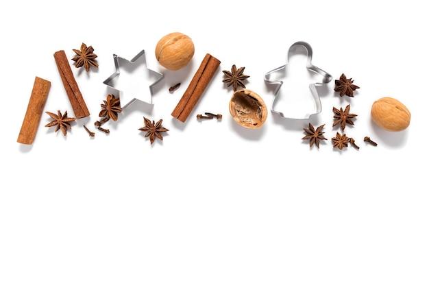 Anice stellato, bastoncini di cannella, spezie profumate, noci e forme di biscotti isolano su una superficie bianca con un posto per il testo