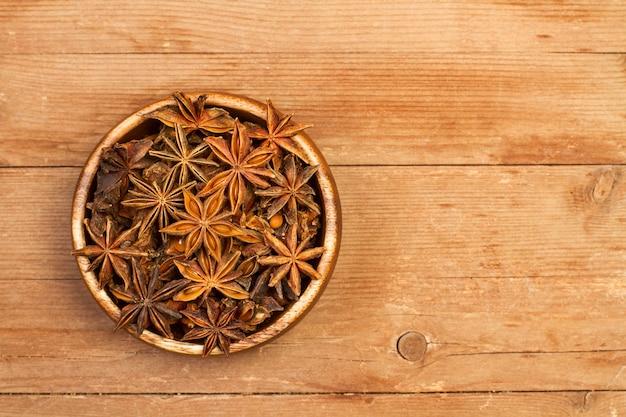Anice stellato in una ciotola di legno su un tavolo in legno rustico