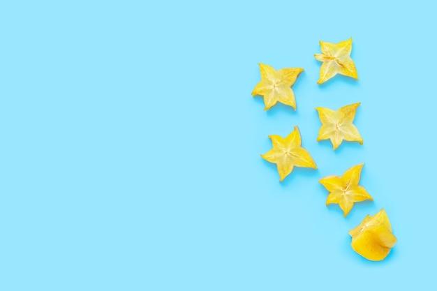 Fette di frutta a stella su superficie blu