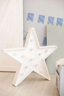 Lampada a stella sul pavimento di una parete grigia con bandiere natalizie. grande stella con lampadine. decorazione domestica moderna. stella decorativa con lampade. lampada a led bianca a forma di stella lampada monogramma