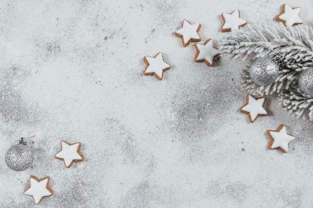 Biscotti a forma di stella e decorazioni natalizie su sfondo bianco. concetto di vacanze invernali. vista dall'alto, spazio libero per il testo