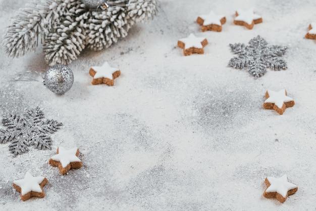 Biscotti a forma di stella e decorazioni natalizie su sfondo bianco. concetto di vacanze invernali.