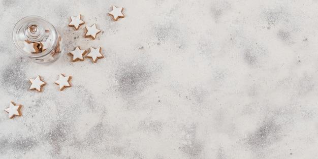 Biscotti a forma di stella e decorazioni natalizie su sfondo bianco