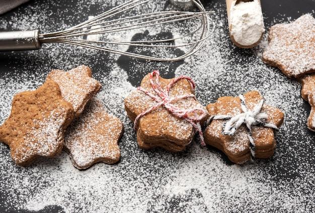 Biscotti di pan di zenzero al forno a forma di stella cosparsi di zucchero a velo su una tavola nera, vista dall'alto