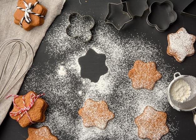 Biscotti di pan di zenzero al forno a forma di stella cosparsi di zucchero a velo su un tavolo nero, vista dall'alto