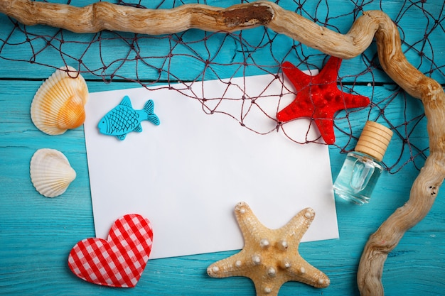 Stelle marine, ciottoli e conchiglie che si trovano su un fondo di legno blu con la cartolina
