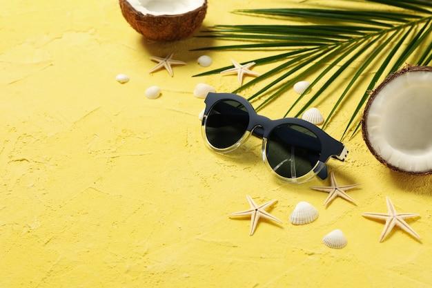 Stelle marine, cocco, ramo di palma e occhiali da sole sulla superficie gialla