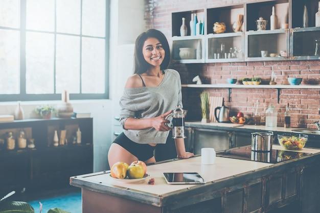 Iniziando la mia giornata con un caffè fresco. bella giovane donna di razza mista che tiene in mano un barattolo con caffè e sorride mentre si trova in cucina a casa