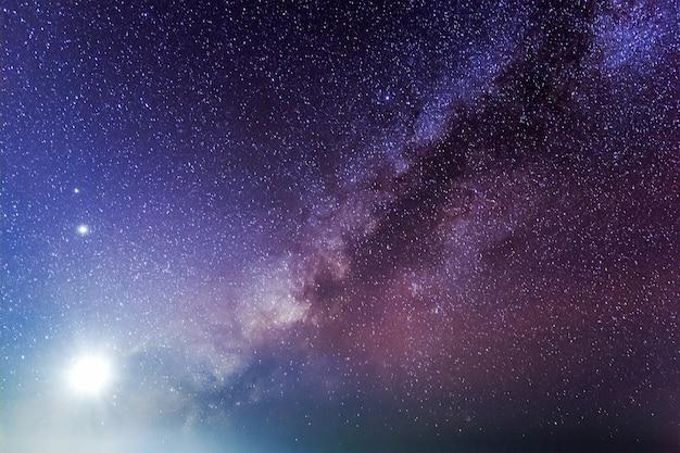 Paesaggio notturno stellato con chiaro di luna e via lattea