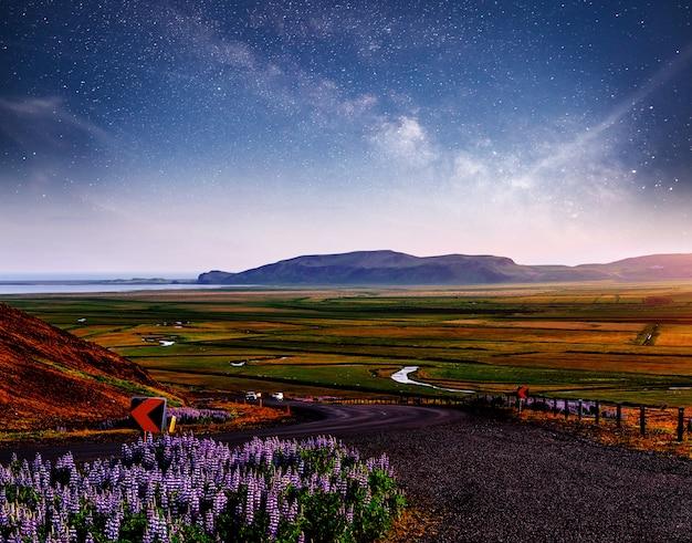 Cielo stellato sopra le montagne. la strada asfaltata con macchie bianche. islanda