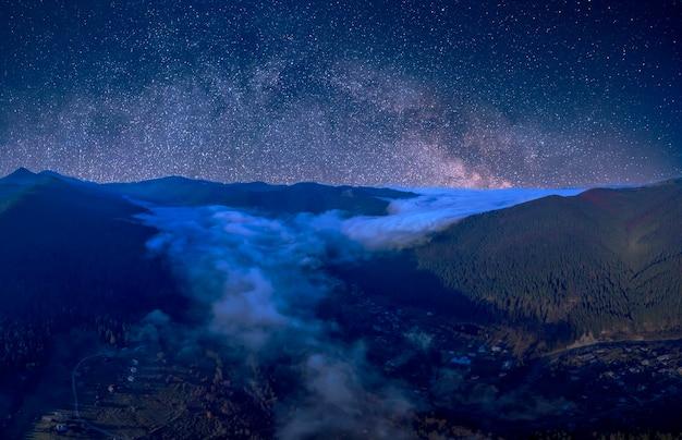 Cielo stellato sopra le cime delle montagne boscose. la nebbia si sta diffondendo negli intermontani. meraviglioso paesaggio di montagna notturno.