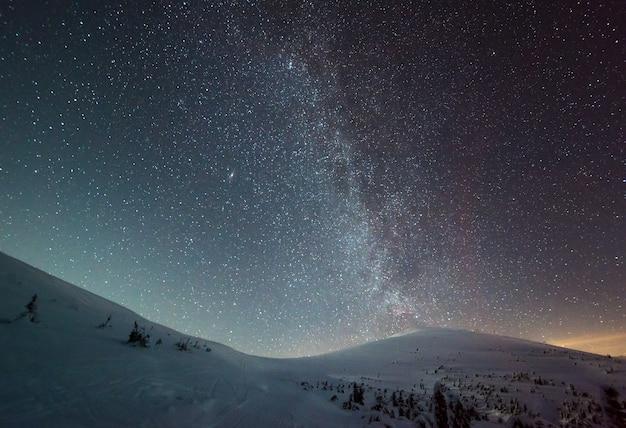 Il cielo stellato con foschia rosa si trova sopra la stazione sciistica invernale