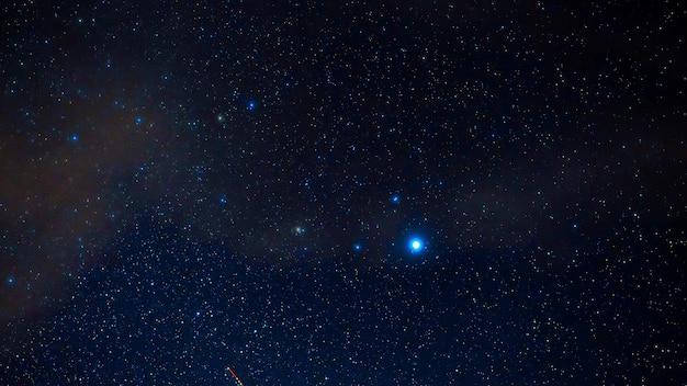 Cielo stellato con costellazioni brillanti e stelle cadenti di notte. timelapse del cielo stellato con nuvole, nebulose e galassie