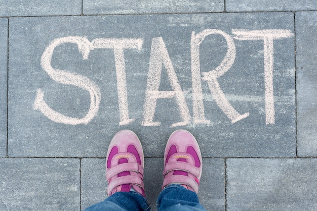 Inizia il concetto. le gambe della ragazza del bambino che stanno sul marciapiede davanti alla parola di inizio del gesso scritta a mano. di nuovo a scuola
