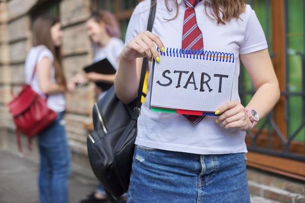 Inizio. una studentessa tiene il taccuino con l'inizio della parola, l'inizio delle lezioni a scuola, al college. edificio in mattoni e sfondo di studenti parlanti