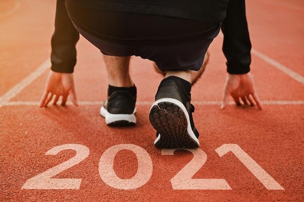 Inizio dell'uomo che corre sul campo da corsa inizio dei piani del nuovo anno obiettivo di successxa