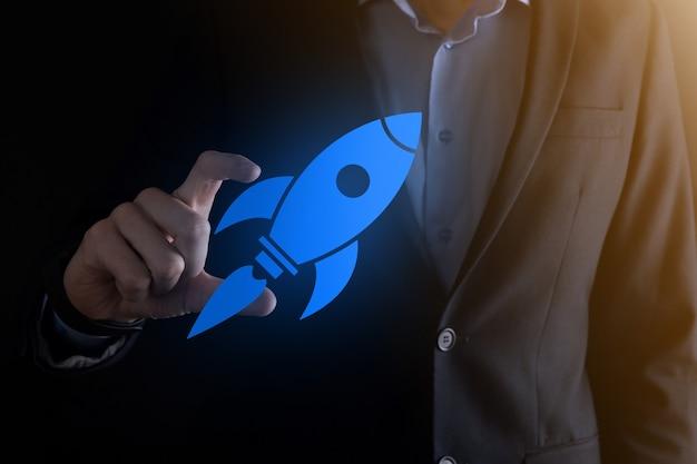 Il concetto di avvio con l'uomo d'affari che tiene il razzo astratto dell'icona digitale sta lanciando il volo in volo