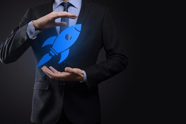 Il concetto di avvio con l'uomo d'affari che tiene in mano l'icona del razzo digitale astratto il razzo sta lanciando e vola in volo