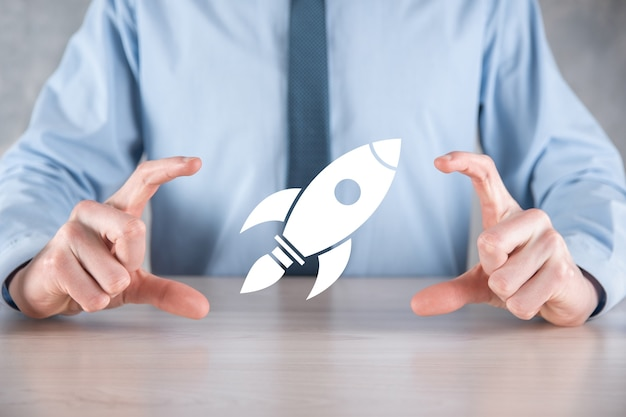 Avviare il concetto con l'uomo d'affari che tiene il razzo digitale astratto dell'icona del razzo sta lanciando e salire volando.
