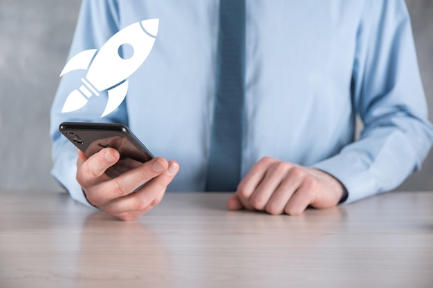 Avviare il concetto con l'uomo d'affari che tiene l'icona del razzo digitale astratto il razzo sta lanciando e vola in
