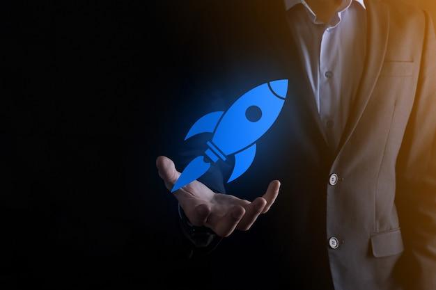 Il concetto di avvio con l'uomo d'affari che tiene in mano l'icona del razzo digitale astratto sta lanciando e volando