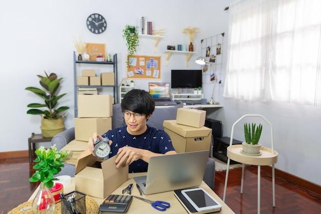 Avviare il giovane imprenditore asiatico dell'uomo di piccola impresa che prepara i pacchi che imballano la scatola di cartone