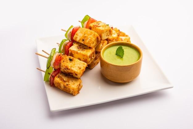 Spuntino di avviamento paneer tikka con bastone nel piatto con chutney verde isolato su bianco. piatto della cucina indiana con ricotta alla griglia con verdure e spezie