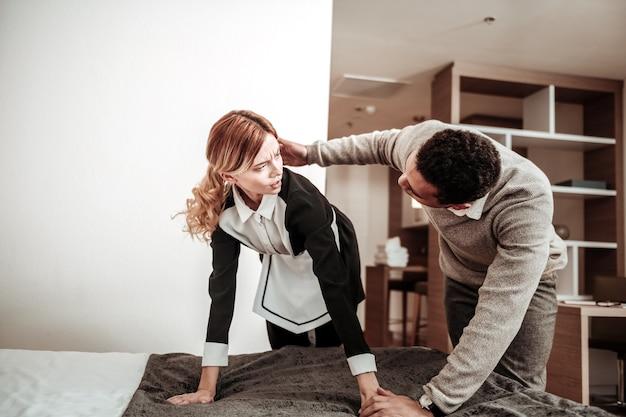 Inizio molestie. cliente dai capelli scuri dell'hotel che inizia a molestare la giovane cameriera