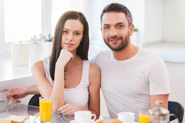 Iniziare un nuovo giorno insieme. bella giovane coppia che si lega l'una all'altra mentre si siede in cucina insieme e fa colazione