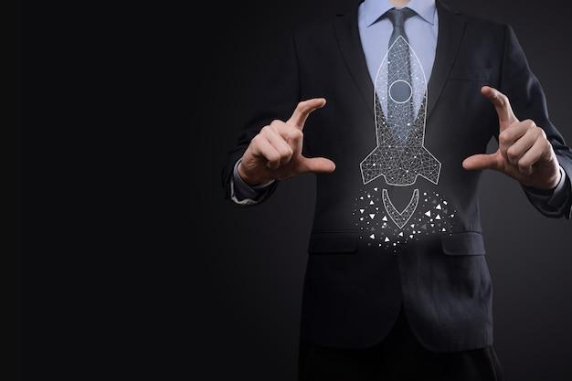 Il concetto di attività di avvio, l'uomo d'affari che tiene l'icona razzo trasparente sta lanciando e vola fuori dallo schermo con connessione di rete su sfondo scuro.
