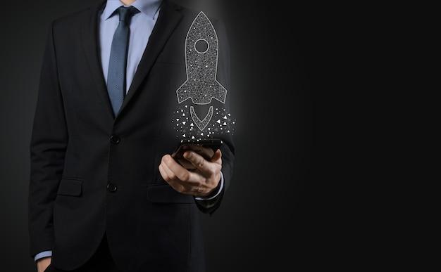 Il concetto di avvio dell'attività, l'uomo d'affari che tiene l'icona razzo trasparente sta lanciando e volando fuori dallo schermo con connessione di rete su sfondo scuro.