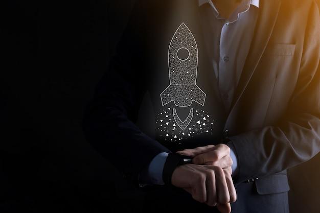 Il concetto di avvio dell'attività, l'uomo d'affari che tiene l'icona razzo trasparente sta lanciando e vola fuori dallo schermo con connessione di rete su sfondo scuro