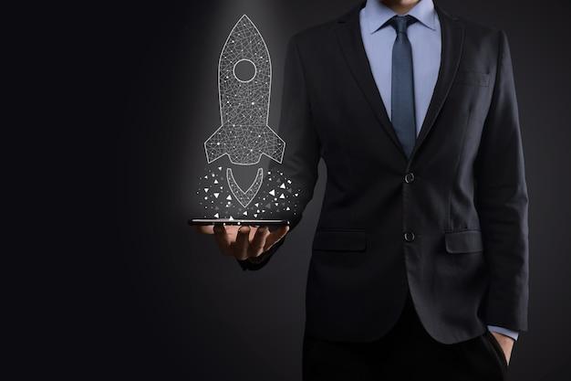 Il concetto di affari di avvio, uomo d'affari che tiene icona trasparente razzo sta lanciando e salire volando fuori dallo schermo con connessione di rete sul muro scuro