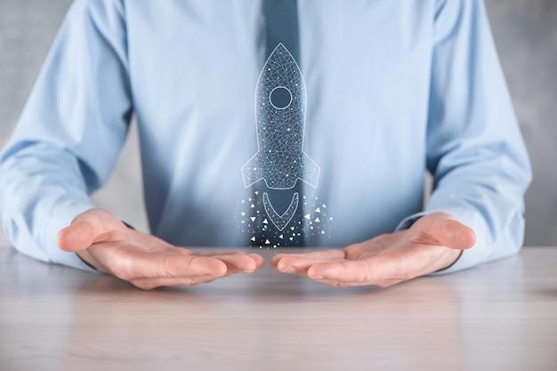 Il concetto di affari di avvio, uomo d'affari che tiene icona trasparente razzo sta lanciando e vola fuori dallo schermo con connessione di rete sulla parete scura.