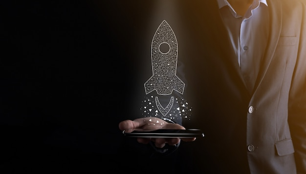 Il concetto di affari di avvio, uomo d'affari che tiene icona trasparente razzo sta lanciando