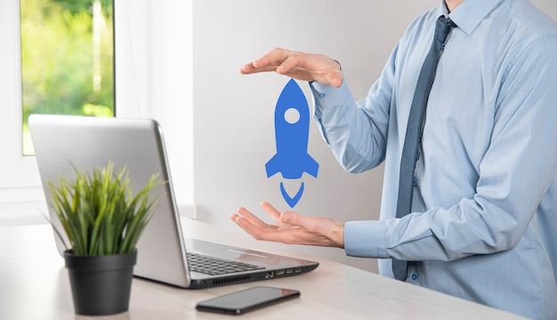Il concetto di business di avvio, l'uomo d'affari che tiene tablet e icona razzo sta lanciando e vola fuori dallo schermo con connessione di rete su sfondo scuro.