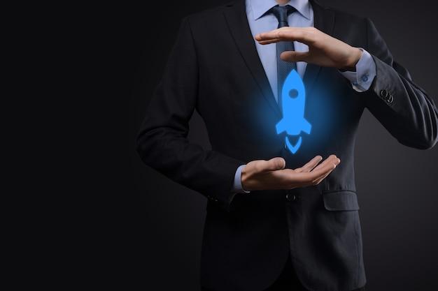 Il concetto di affari di avvio, uomo d'affari che tiene tablet e icona razzo sta lanciando e vola fuori dallo schermo con connessione di rete su sfondo scuro.