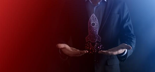 Il concetto di affari di avvio, uomo d'affari che tiene tablet e icona razzo si sta lanciando e vola fuori dallo schermo con connessione di rete su sfondo scuro.