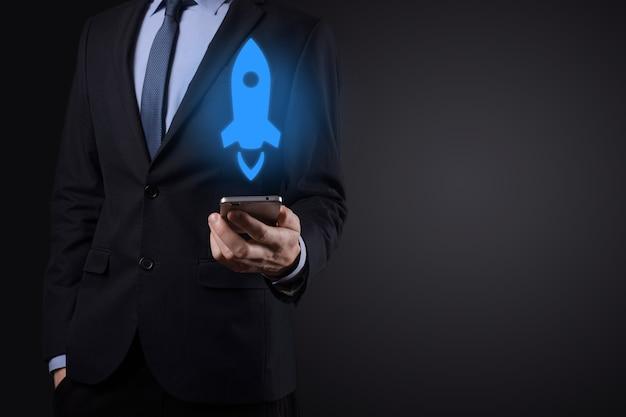 Il concetto di business di avvio, l'uomo d'affari che tiene il tablet e il razzo icona sta lanciando e volando fuori dallo schermo con connessione di rete su sfondo scuro.